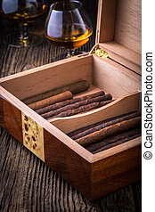 humidor with quality cigar and cognac