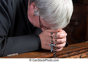 Humble priest kneeling down and praying with his rosary