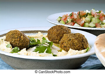 Falafel balls with hummus, arabic salad, pita and a tahini sauce.