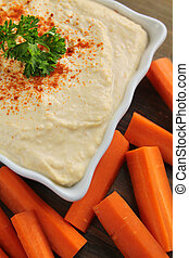 Hummus - Top view of hummus with carrots on a wooden table