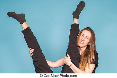 Humor, april fools day and fun concept - Smiling woman hugs men's legs