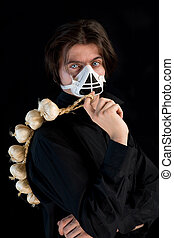 Humorous shot of vampire in respirator holding garlic