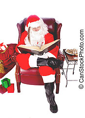Humorus closeup of Santa Claus (that jolly old elf that lives at the North Pole) reading and writing in the book of good children