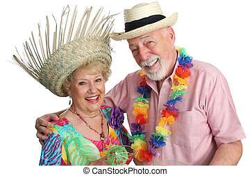 An attractive elderly couple on a tropical vacation, laughing together. Isolated