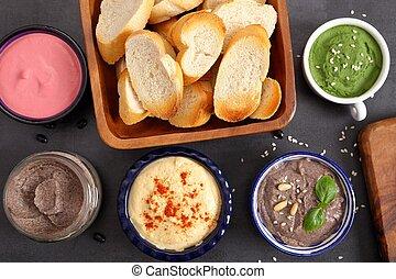 Humus and bread. - Different types of humus in ceramic...