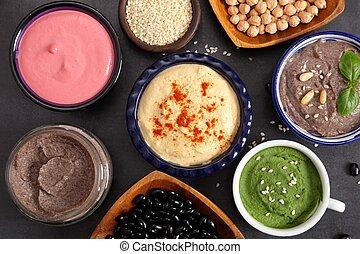 Humus. - Different types of humus in ceramic bowls. Top...