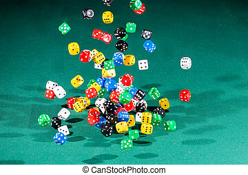 Hundred colored dices falling on a green table
