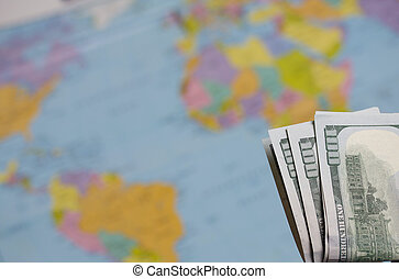Hundred dollar banknotes. Against the background of a world map. The silhouettes of South America and Africa are visible on it.