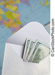 Hundred dollar banknotes. Lie in an open paper envelope. Against the background of a world map. The silhouettes of South America and Africa are visible on it.