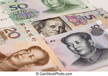 Hundred dollar bill surrounded by Chinese Yuan