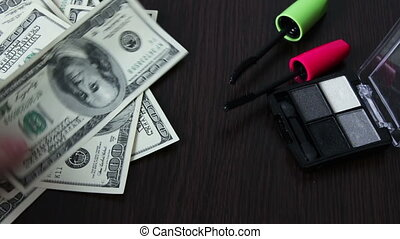Hundred dollar bills and cosmetics on the table. - Hundred...