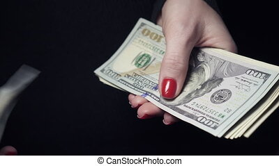 hundred dollar bills in female hands - woman counting...