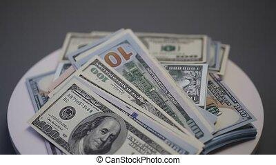 Hundred dollar bills spinning on a table.