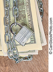 Hundred dollars banknotes secured with a chain and lock.
