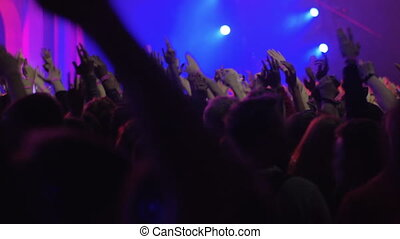 Hundreds of excited people dancing at the concert, view with bright stage lights