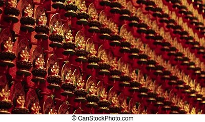 Hundreds of identical, miniature Buddha statues in neat rows, mounted on the wall inside the Buddha Tooth Relic Temple in Singapore.