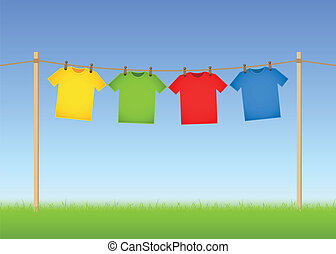 Hung T-shirts on washing line with grass and blue sky in the...