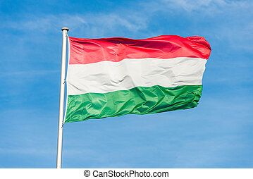 Hungarian flag waggling in the wind with sky in background
