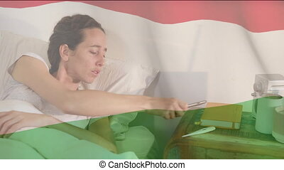 Animation of Hungarian flag waving over a sick Caucasian woman lying in bed coughing using smartphone. Global coronavirus pandemic concept digitally generated image.