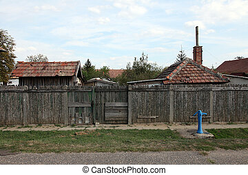 Rural houses behind high wooden fence. Blue hydrants in front of fence in the street.