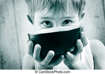 Hunger - a young boy in monotone peeks over an empty rice...