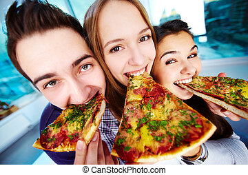 Hunger - Image of happy teenage friends eating pizza and...