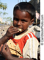 A hungry and dirty boy from the Indian slums eating food.