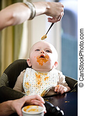 Hungry baby eating solid food from a spoon