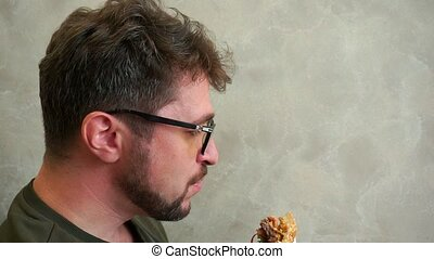 Hungry bearded man with glasses eating a delicious hamburger. He sits in a cafe