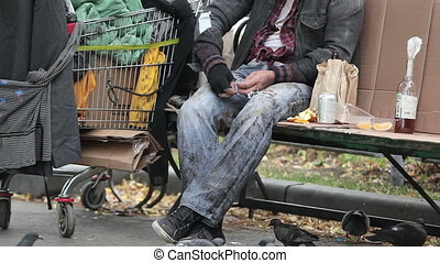 Tilt of a homeless guy feeding the pigeons with bread crumbs