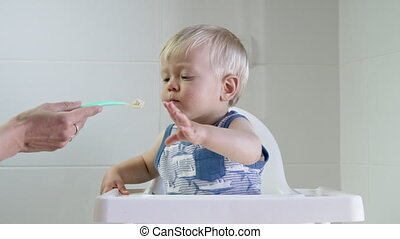 Hungry blond toddler eating porridge - Hungry blond toddler...
