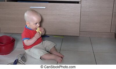 Hungry boy eat food sitting in mess on kitchen floor. Static...