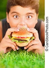 Hungry boy eating burger