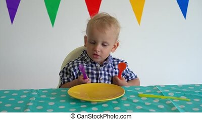 hungry boy with fork and spoon sitting in front empty plate. Gimbal motion