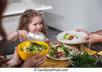 Hungry child eating vegetables with mom and dad