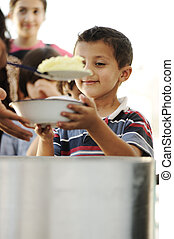 Hungry children in refugee camp, distribution of ...