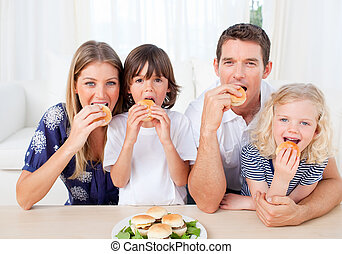 Hungry family eating burgers in the living room at home