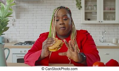 Charming hungry obese african american woman with afro braids enjoying eating harmful fast food, biting appetizing hamburger greedly, looking satisfied and happy in domestic kitchen.