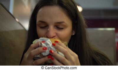 Hungry girl eating hamburger. Woman biting cheeseburger at fast food restaurant