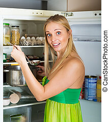 hungry  girl eating  soup from pan near fridge