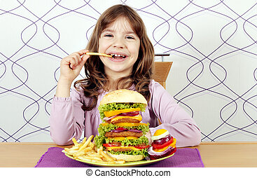 hungry little girl eat big hamburger and french fries