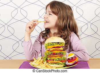 hungry little girl eat french fries and big hamburger
