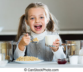 Hungry little girl with milk and oatmeal kasha