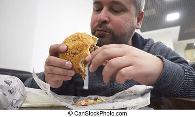 Hungry man eating big hamburger in fast food cafe