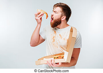 Hungry man eating slice of pizza isolated on white...