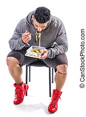 Hungry muscular man gulping down food