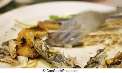 Hungry person turns over the remains of eaten fish on a...