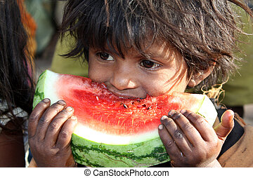 A hungry poor girl from India eating a fresh watermelon.