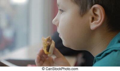 hungry teenager eats junk food. Close-up. Burger, cheeseburger, sandwich