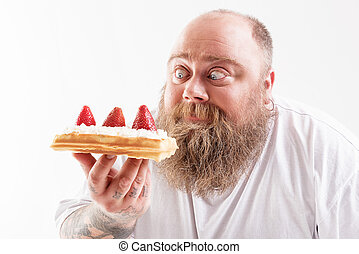 Hungry thick guy staring at sweet food